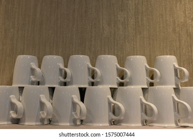 Stack of small ceramic cups on shelf, Pile of Clean ceramic coffee cups,Close up of a Stack of clean mint cups on shelf in cafe.
