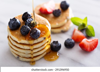 Stack of small pancakes with berries on marble board