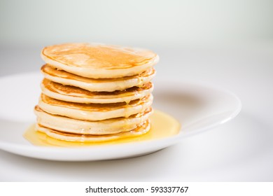 Stack of Small pancakes in syrup