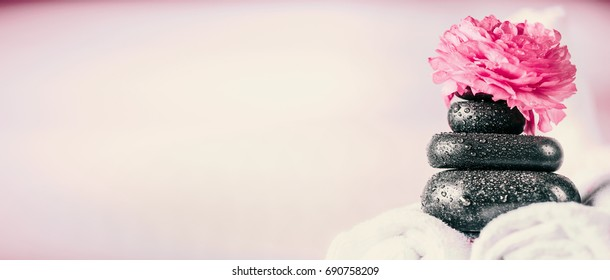 Stack of spa massage stones with pink flowers and  towels, wellness background, front view, banner