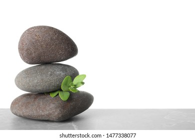 Stack of spa stones and green leaves on table against white background. Space for text