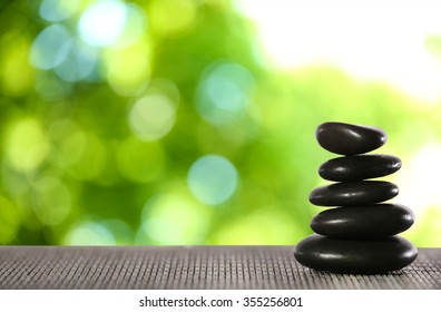Stack of spa stones on bamboo mat against blurred nature background