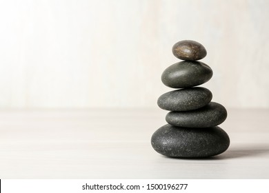 Stack of spa stones on table against white background, space for text