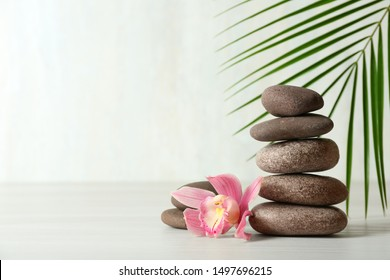 Stack of spa stones, palm leaf and flower on table against white background, space for text