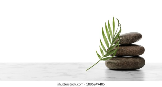Stack of spa stones and tropical leaf on marble table against white background. Space for text