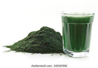 Stack of spirulina algae powder and spirulina drink isolated on white background