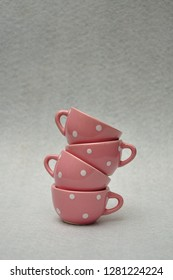 A stack of spotted porcelain tea cups