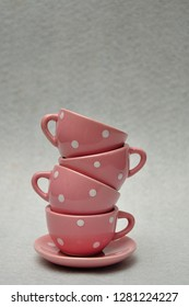 A stack of spotted porcelain tea cups on top of a plate