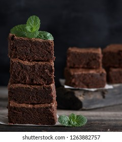 stack of square pieces of baked brown brownie pie on a wooden  board
