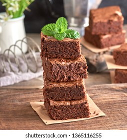 stack of square pieces of baked brownie on a brown wooden board, on top of a cake of mint leaf