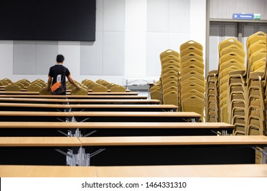 Stack Steel Chair Fabric seat pad yellow gold color and Table arrange in row ready to set up for big meeting, conference, business in Convention Hall of Hotel, worker carry chair with motion blur