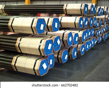 Stack of steel pipes in industrial warehouse.