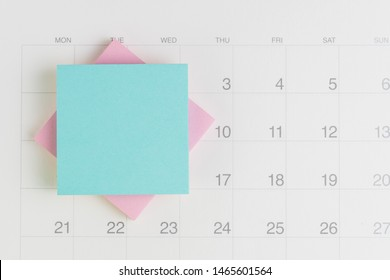 Stack of sticky note or adhesive paper with black space for writing message on white clean calendar using as reminder for vacation, project launch date or special event message.