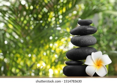 Stack of stones with flower and blurred green leaves on background, space for text. Zen concept