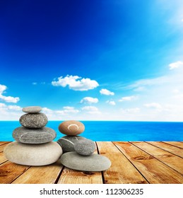 Stack of stones with mint leaf on wood planks with view on beauty sea under blue clouds sky. Alternative medicine concept