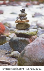 Stack of stones on the banks of the turbulent Verzasca River in Europe Alps - meditation and calm land art of people travelers in Switzerland