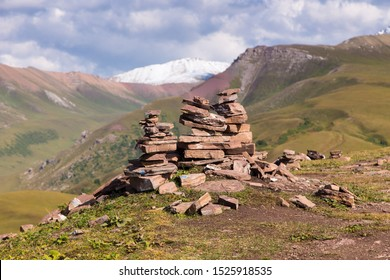 Stack of stones rocks trail marker cairn in the mountains. Against the backdrop of snowy mountains high in the mountains. Kyrgyzstan, Karakol. Hiking, climbing mountains, waypoint.