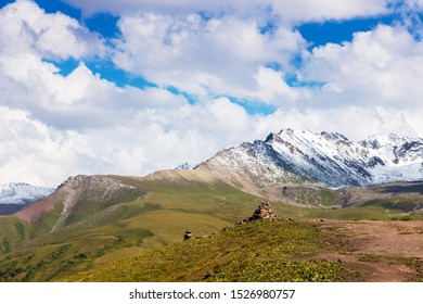 Stack of stones rocks trail marker cairn in the mountains. Against the backdrop of snowy mountains high in the mountains. Kyrgyzstan, Karakol