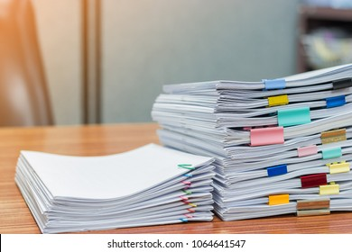 Stack of student's homework that assigned to students to be completed outside class on teacher's desk separated by colored paper clips. Document stacks arranged by various colored paper clips on desk.