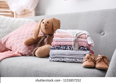 Stack of stylish child clothes, shoes and toy bunny on couch indoors