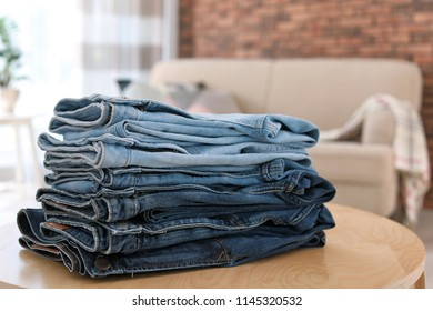 Stack of stylish jeans on table against blurred background
