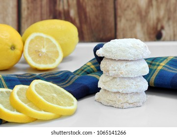 A stack of sugared lemon cookies, with whole and sliced lemons.