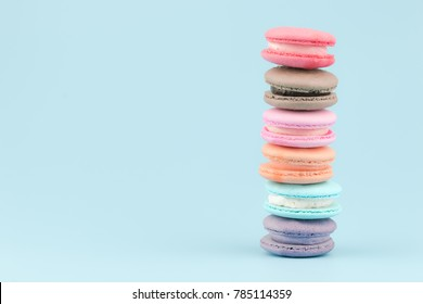 Stack of sweet french macaroons cake (or macarons) with vintage pastel colored tone on blue background.