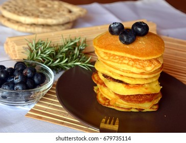 Stack of sweet homemade pancakes with fresh blueberries on a plate.