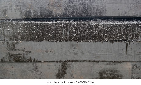 A stack of tarred timbers, old railway wooden black sleepers, with smudges of tar on the surface, lying on top of each other in several rows. Industrial background.