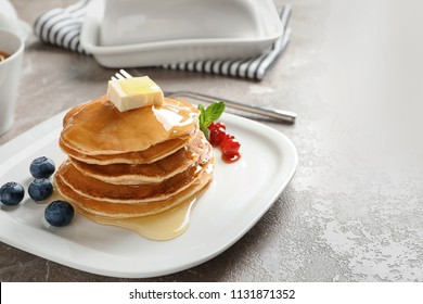 Stack of tasty pancakes with berries, butter and honey on table