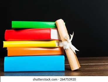 Stack Of Text Books And Graduation Scroll