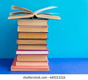 A stack of textbooks and fiction on a blue background. Open book with pages