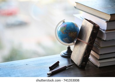 A stack of textbooks on the windowsill and writing utensils. Headphones for music and an open book on the windowsill. Student Headphones Globe and Books Accessories on a Wooden Table