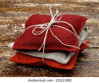 Stack of Textile Sachet Pillows with Sack Rope and Bow on Textured Wooden background