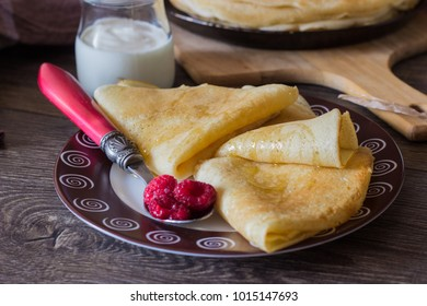 Stack of thin pancakes (bliny) or crepes with raspberry and sour cream. Traditional for the Russian pancake week (Maslenitsa).