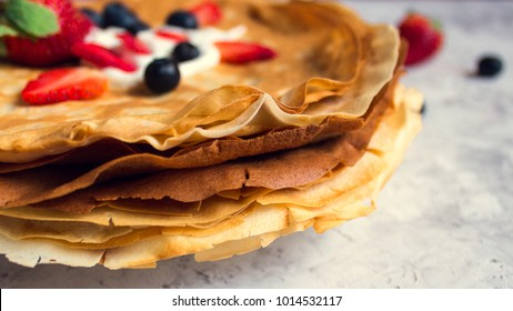 Stack of thin pancakes poured with sour cream and decorated with fresh strawberries and blueberries side view with selective focus. The concept of Russian holiday Maslenitsa, Shrovetide.