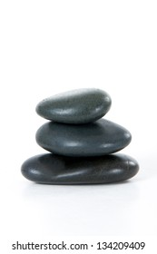 Stack of three black massage stones, isolated on white background.