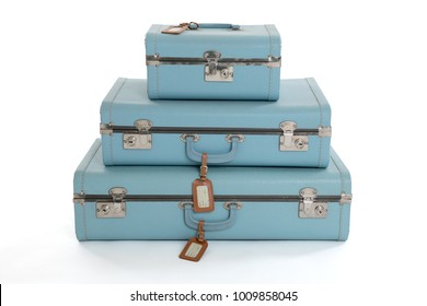 Stack of three blue vintage hard suitcases isolated on a white background