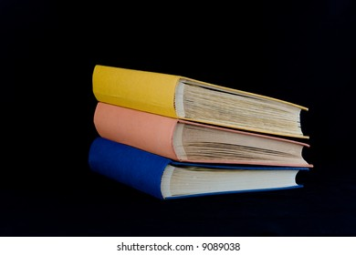 Stack of three books,with yellow, orange, and blue covers. Isolated against black background.