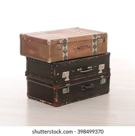 stack of three brown retro suitcases on floor on white studio background