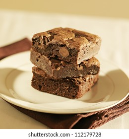 Stack of three brownies on a plate.