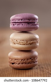 A stack of three colorful French macarons on a dark rustic wooden table.