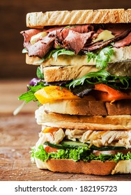 Stack of three delicious toasted sandwiches with different fillings including rare roast beef,shredded chicken breast and pepper and cheese all garnished with herb and salad ingredients,close up view
