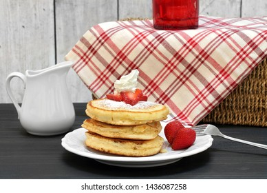 A stack of three pancakes, garnished with fresh strawberry slices and whipped cream.  Pancakes are custed with powdered sugar.