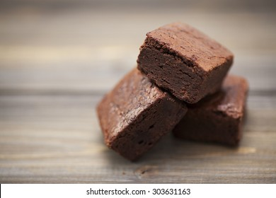 Stack of three pieces of chocolate brownie cake on a wooden background.