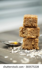 Stack of three pieces of flapjack on a wooden background. Scattering of rolled oats and a spoon full of golden syrup (two of the main ingredients in flapjacks)