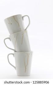 Stack of three used white coffee mugs on white