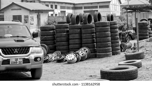 Stack of tires with a house and a car in background. Auto market in West Africa. Urban landscape. Black white photography.  Ghana, Accra, Tema - January 19, 2017