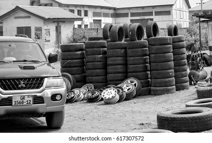 Stack of tires with a house and a car in background. Auto market in West Africa. Urban landscape. Modern lifestyle in developing countries. Black white photography.  Ghana, Accra, Tema - January 19, 2