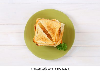 stack of toasted bread slices on green plate